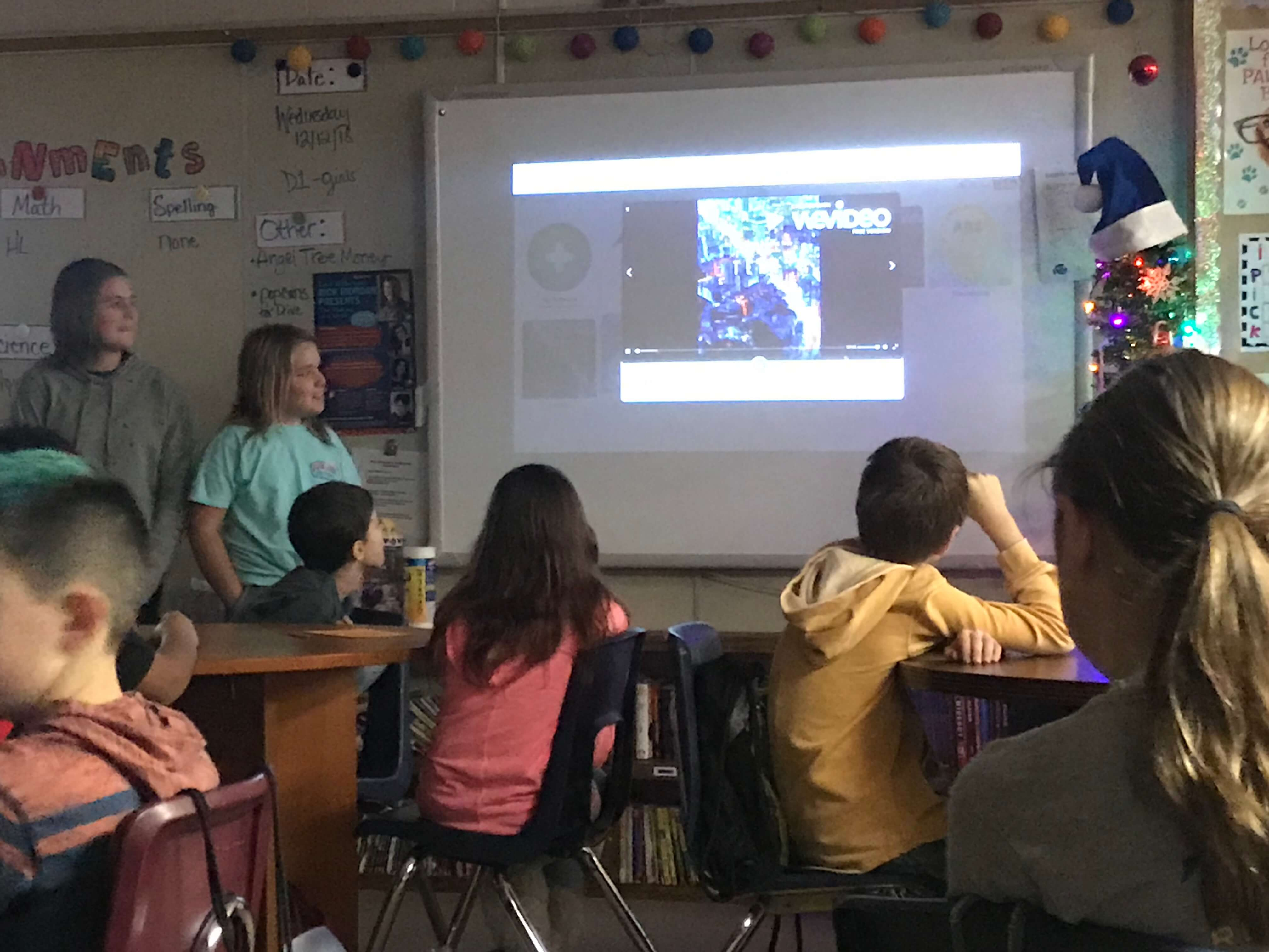 students in a classroom looking at projector presentation