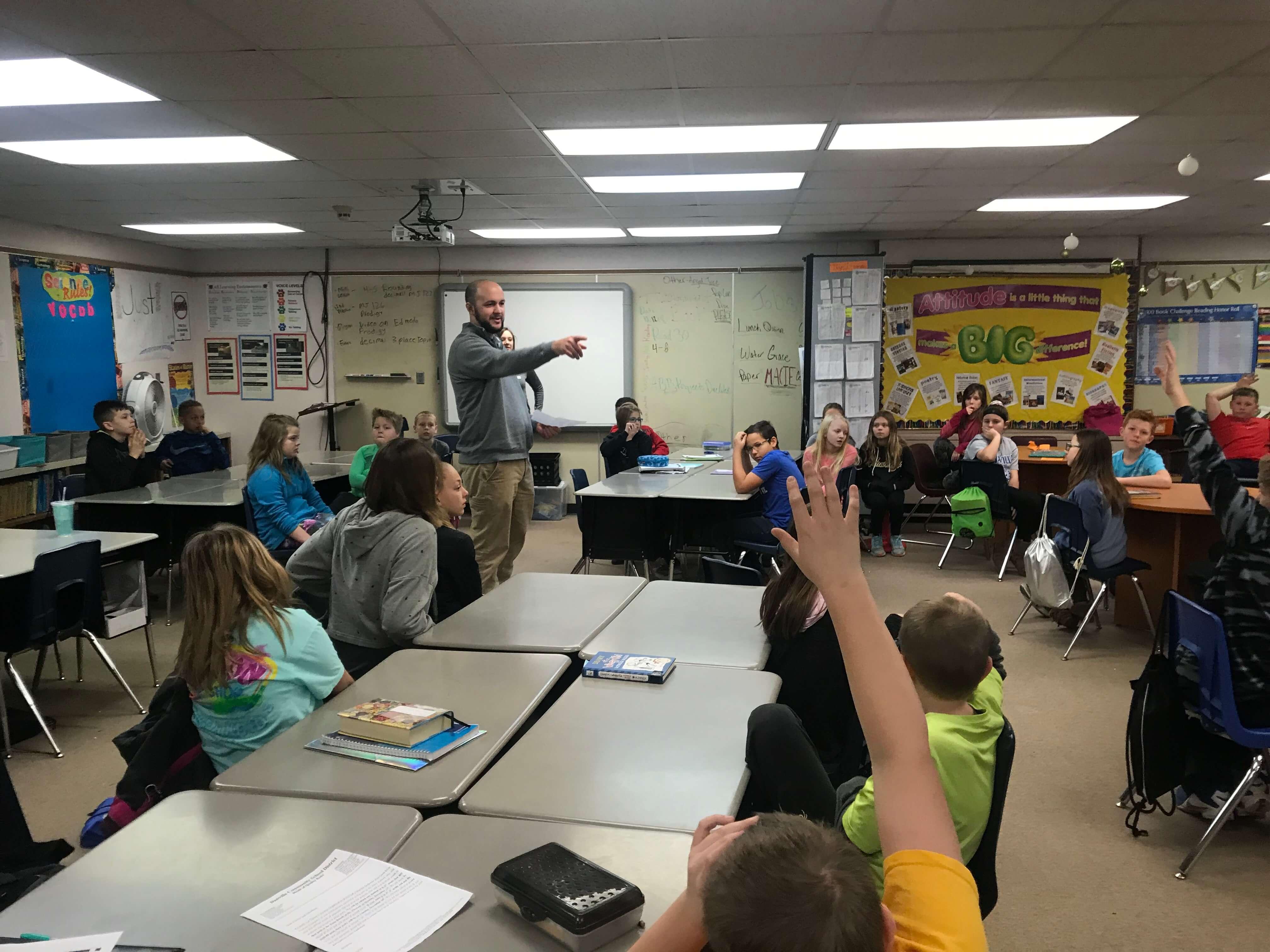 teacher calls on students raising their hands